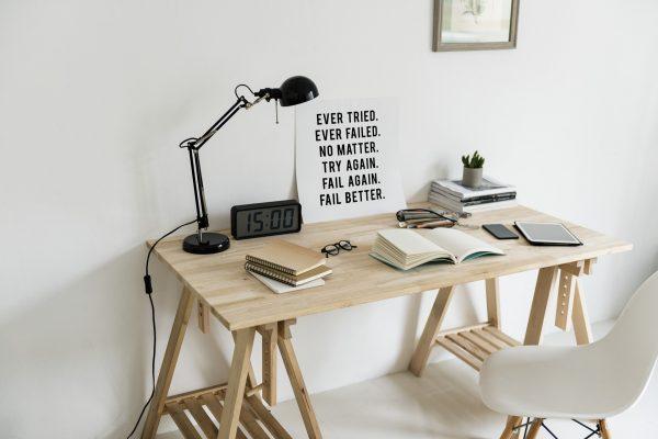 sebuah ruangan yang etrdapat mea kerja dengan buku - buka dan lampu baca diatasnya