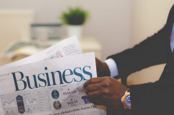 pemilik perusahaan yang sedang membaca koran tentang bisnis