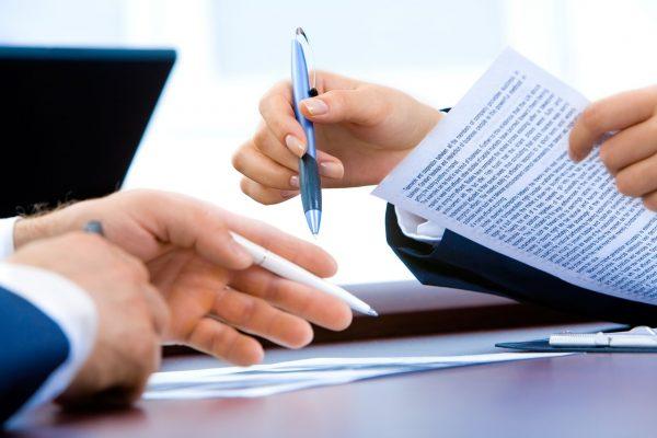tangan dua orang yang sedang memegang dokumen legalitas perusahaan