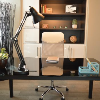 ruang kerja berisi satu set meja dan kursi, rak buku dan lampu baca diatas meja