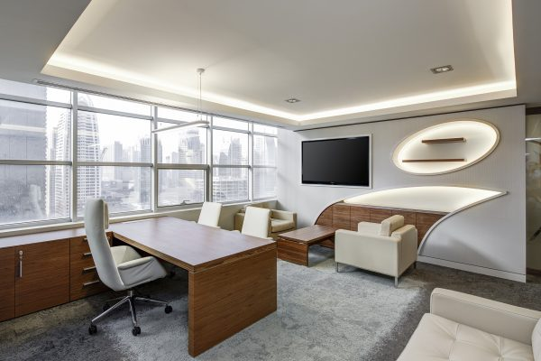 ruang kerja dengan satu set meja dan kursi serta lcd tv di dinding dan sofa dibawahnya